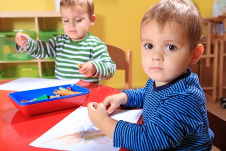 gemelas: Lindos ni�os peque�os europeos dibujar una imagen en el jard�n de infantes.  Foto de archivo
