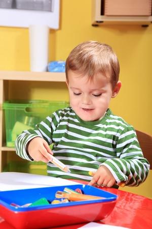 Lindo niño pequeño caucásico dibujar una imagen en el jardín de infantes.