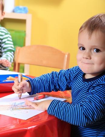 kindergarten toys: Cute caucasian toddler drawing a picture in kindergarten.