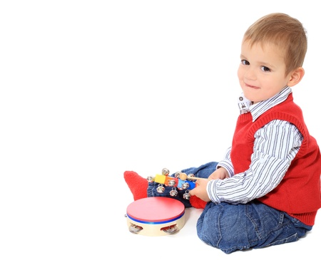 music instruments: Cute caucasian toddler playing with music instruments. All isolated on white background. Extra copy space on left side.