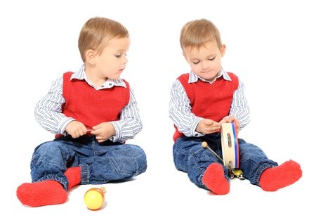 Cute caucasian twin brothers playing with music instruments. All isolated on white background.  photo