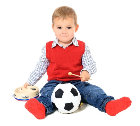 music instruments: Cute caucasian toddler playing with music instruments and soccer ball. All isolated on white background. Stock Photo