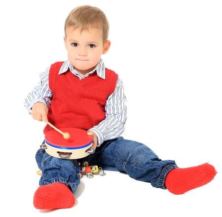 Cute caucasian toddler playing with music instruments. All isolated on white background. Extra copy space on left side.