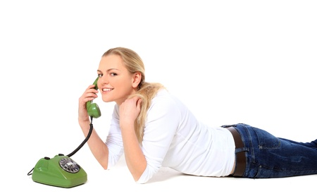Attractive blonde woman making a phone call while lying on floor. All on white background.  Stock Photo - 8588069