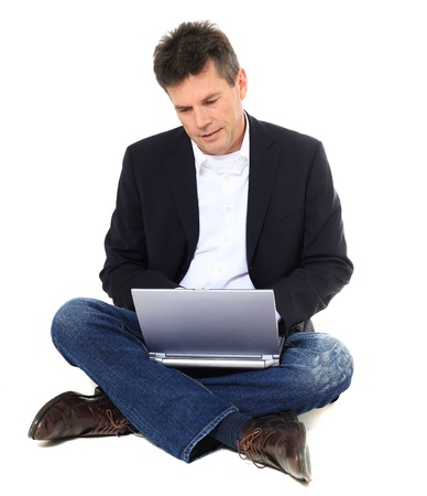 Attractive middle-aged man using notebook computer. All on white background. Stock Photo - 8824887