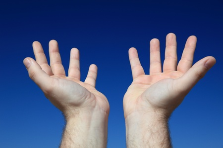 A persons hands praying to the sky.