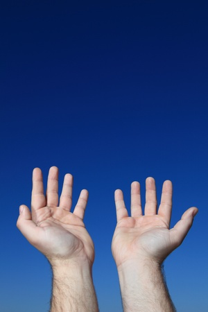 to implore: A persons hands praying to the sky.