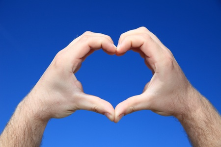 helpfulness: A persons hands forming a heart in front of bright blue sky  Stock Photo