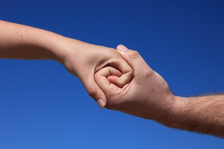 solidarity: Two persons holding hands in front of bright blue sky  Stock Photo