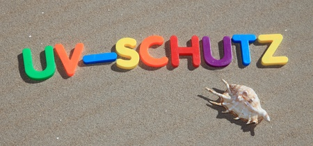 schutz: The german term uv-schutz written in colorful letters on the sand.