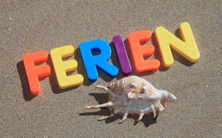 ferien: The german term ferien written in colorful letters on sand. Stock Photo