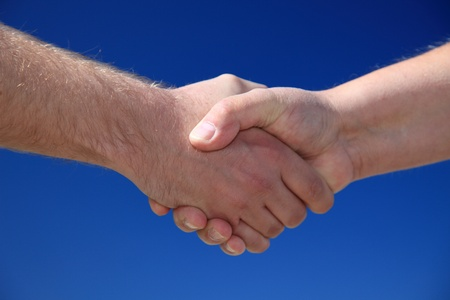 Two persons shaking hands in front of bright blue sky