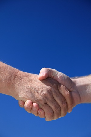 Two persons shaking hands in front of bright blue sky. Stock Photo - 9726337