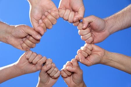Vari popoli le mani davanti al cielo blu brillante. Archivio Fotografico