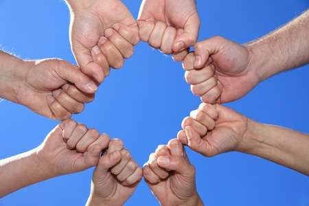 loyal: Various peoples hands in front of bright blue sky.