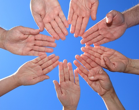 Various peoples hands in front of bright blue sky. Stock Photo - 9726288