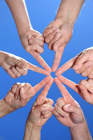 helpfulness: Various peoples hands in front of bright blue sky.