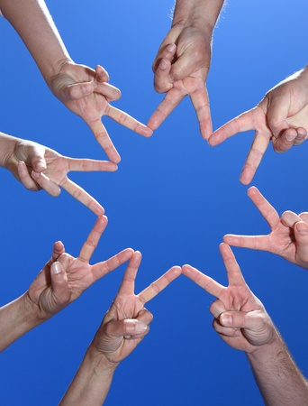 team spirit: Various peoples hands in front of bright blue sky.
