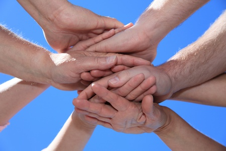 determination: Various peoples hands in front of bright blue sky.