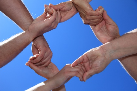cohesion: Various peoples hands in front of bright blue sky.
