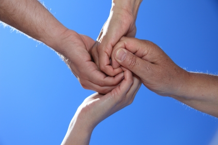 Various peoples hands in front of bright blue sky.