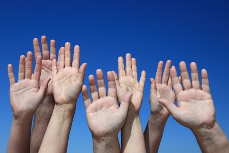 Various hands reaching to the bright blue sky. photo