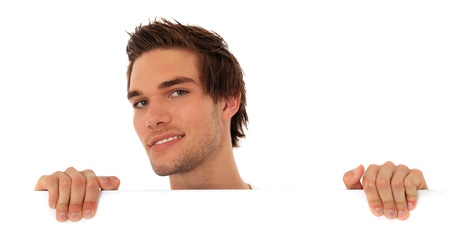 Attractive young man looking from behind a white wall. All on white background. Stock Photo - 9779674