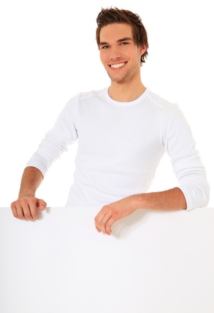 Attractive young man stands behind a blank sign. All on white background. Stock Photo - 9779974