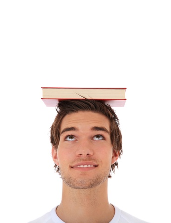 Attractive young man balancing a book on his head. Extra copy space on top. All on white background.  Stock Photo - 9779972