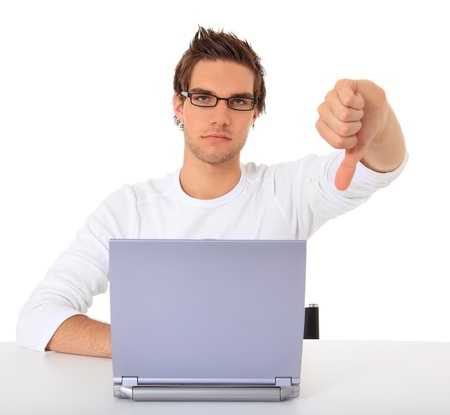 Young guy showing thumbs down while using notebook computer. All on white background.  免版税图像