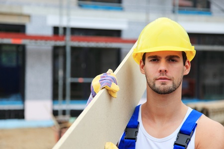 Manual worker on construction site carrying wooden board. Stock Photo - 9781109