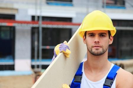 contrema�tre: Travailleur manuel sur le site de construction transportant planche de bois.