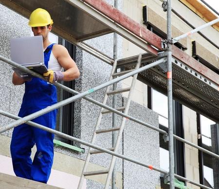 contrema�tre: Ouvrier sur le chantier en utilisant un ordinateur portable.
