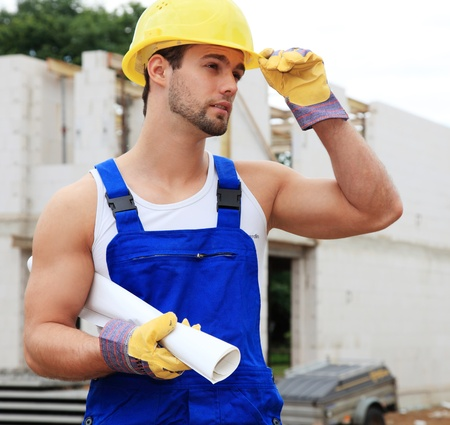 Manual worker on construction site holding plans. Stock Photo - 9852897