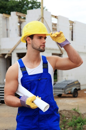 Manual worker on construction site holding plans. Stock Photo - 9781459
