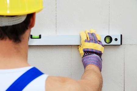 contrema�tre: Travailleur de la construction � l'aide de niveau.