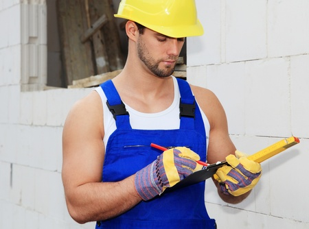 Manual worker on construction site writing on clipboard.  photo