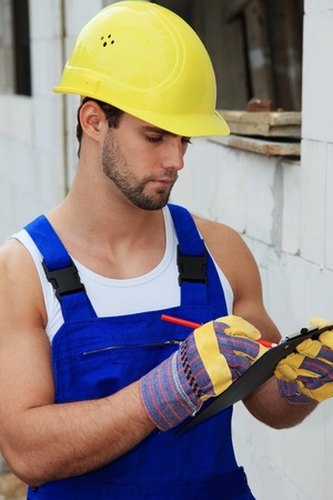 Manual worker on construction site writing on clipboard. Stock Photo - 9781509
