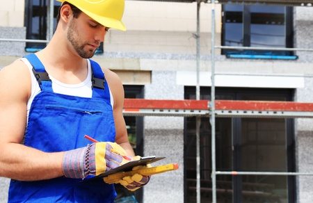 Manual worker on construction site writing on clipboard. Stock Photo - 9778640