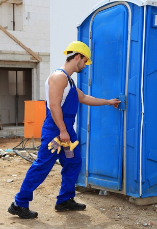 overseer: Manual worker on construction site using the toilet. Stock Photo