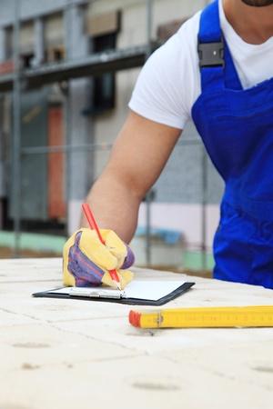 contrema�tre: Ouvrier sur le chantier de construction sur l'�criture presse-papiers.