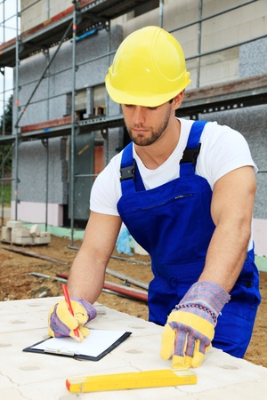 overseer: Manual worker on construction site writing on clipboard.  Stock Photo