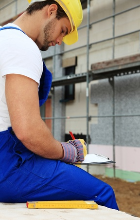 Manual worker on construction site writing on clipboard. Stock Photo - 9781452