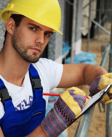 Manual worker on construction site writing on clipboard. Stock Photo - 9781104