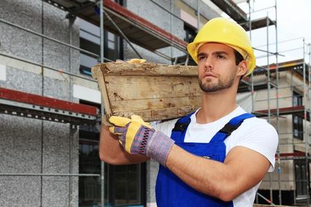 andamio: Trabajador manual en sitio de construcci�n con tabla de madera.