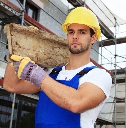 bricklayer: Manual worker on construction site carrying wooden board.