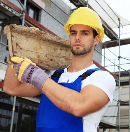 contrema�tre: Ouvrier sur le chantier de construction transportant planche de bois.