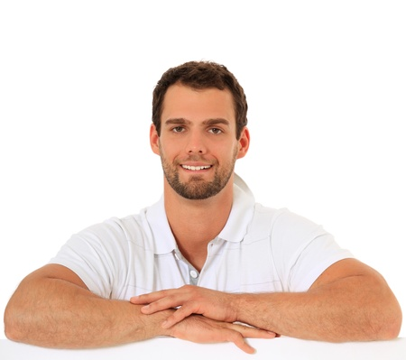 Attractive young guy standing behind white wall. All on white background.  Stock Photo - 9780608