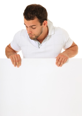 Curious guy standing behind white wall. All on white background. Stock Photo - 9780663