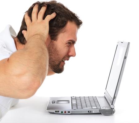 virus informatico: Frustrado hombre sentado frente a su computadora port�til. Todo sobre fondo blanco.  Foto de archivo